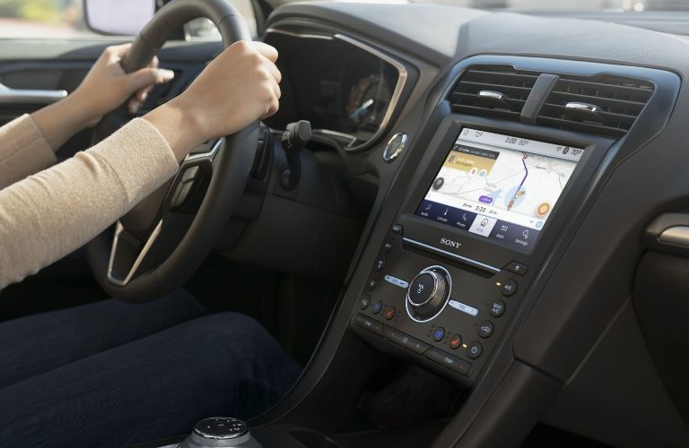 Person with hands on steering wheel of 2020 Ford Fusion also showing dash and infotainment screen