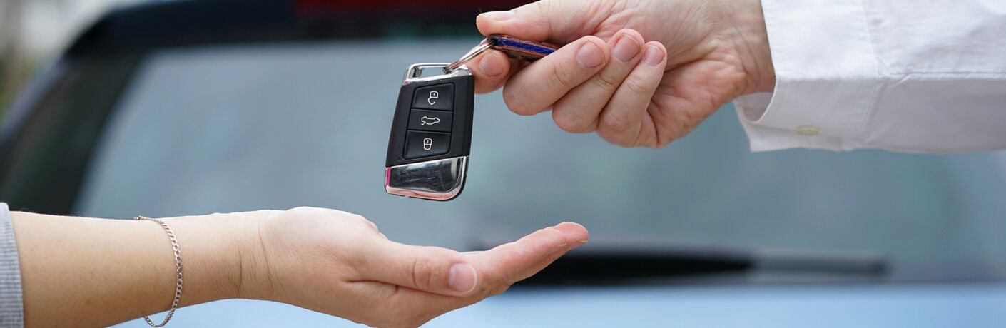 Man handing the keys of a new car to a woman with her palm outstretched