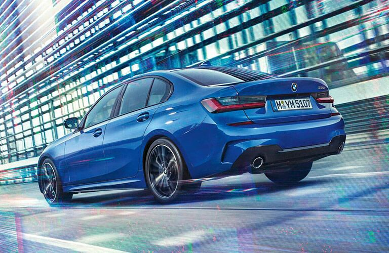 Rear driver angle of a blue 2019 BMW 3 Series driving down a road