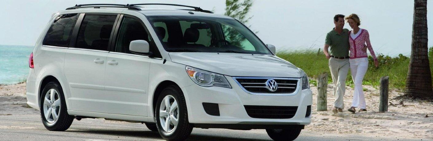 Front passenger angle of a white 2008 Volkswagen Routan with a couple in the background
