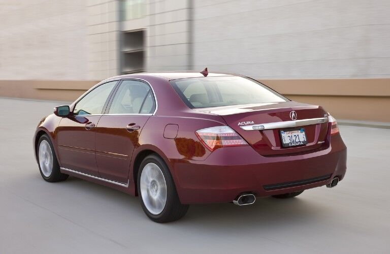 Rear driver angle of a red 2009 Acura RL driving on a street