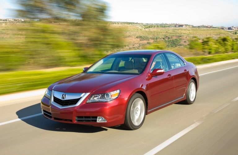 Front driver angle of a red 2009 Acura RL driving on a road