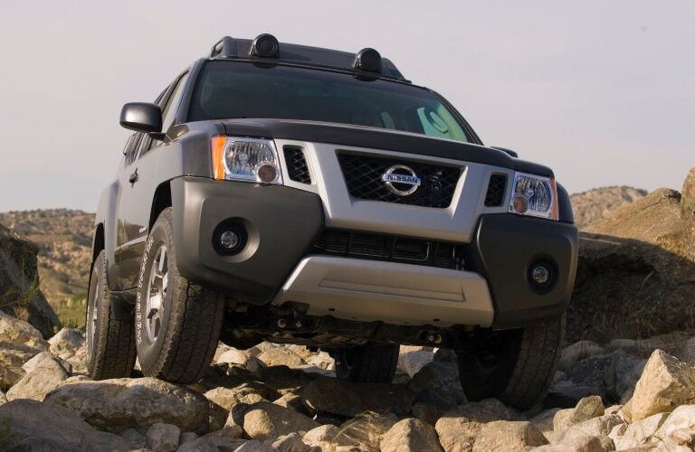 Front angle of a black 2009 Nissan Xterra driving on rocks
