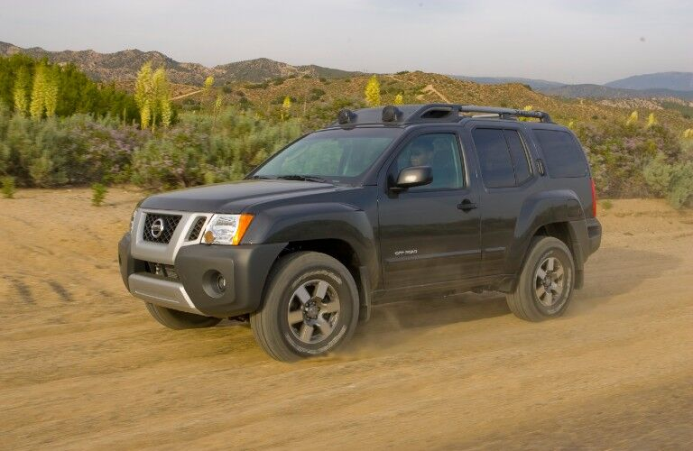 Front driver angle of a black 2009 Nissan Xterra driving on sand