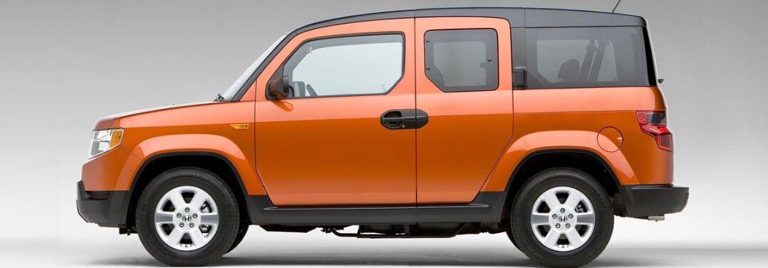 Driver angle of an orange 2011 Honda Element on a grey background