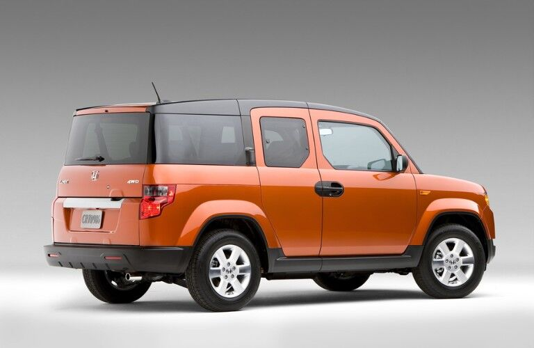 Rear passenger angle of an orange 2011 Honda Element on a grey background
