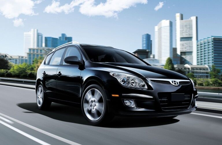 Front passenger angle of a black 2012 Hyundai Elantra Touring driving in a city