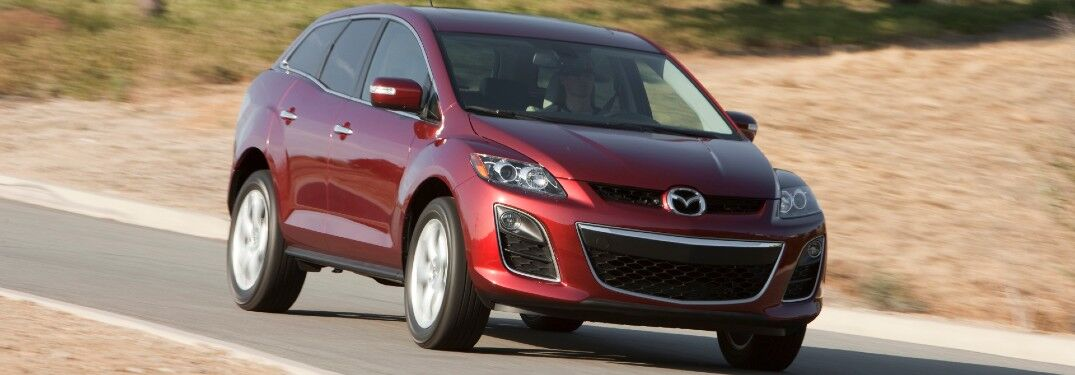 Front passenger angle of a red 2012 Mazda CX-7 driving on a road