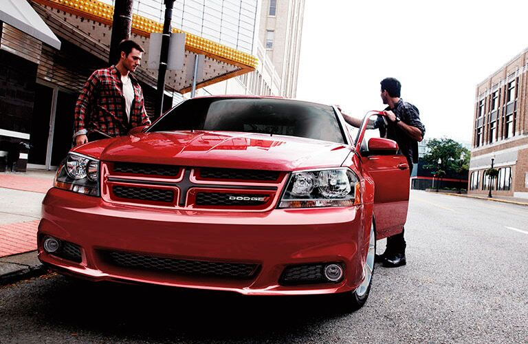 Two men getting into a Dodge Avenger