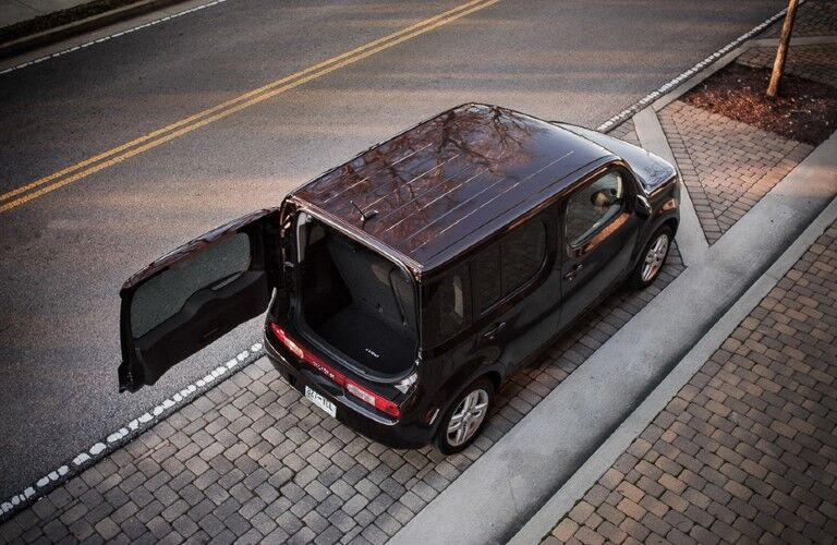 Rear aerial view of a dark colored 2014 Nissan cube with the back door open