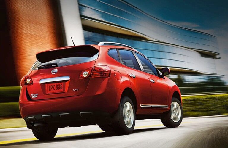 Rear passenger angle of a red 2014 Nissan Rogue Select