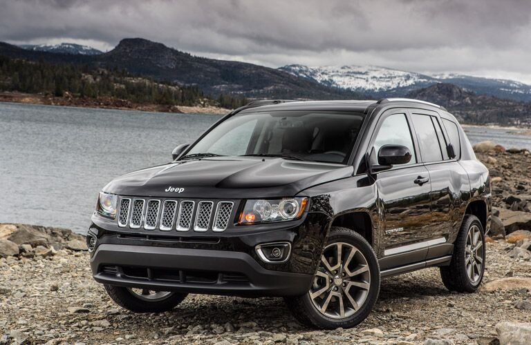 Front profile of the 2016 Jeep Compass parked by a lake and a mountain range