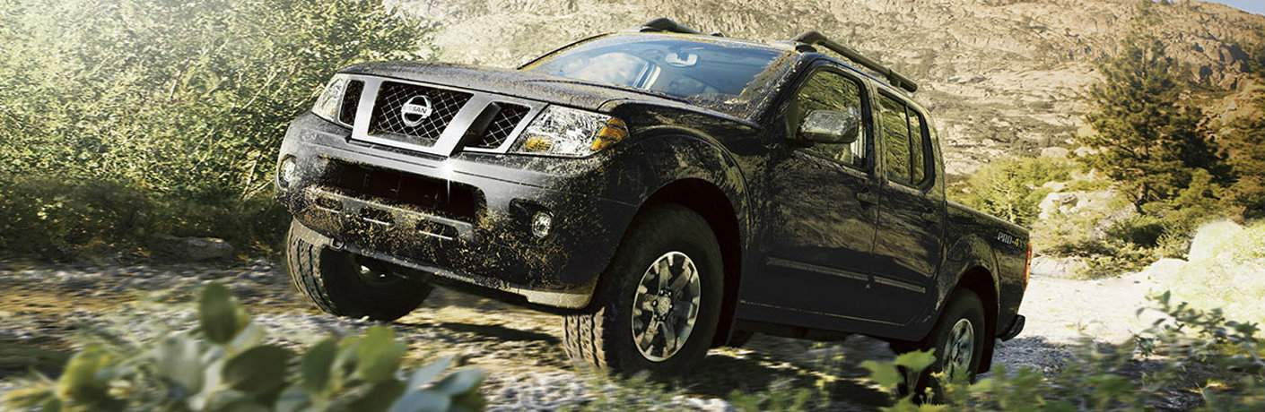 2016 Nissan Frontier driving through a muddy forest with mud on the vehicle