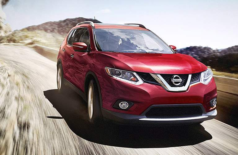 2016 Nissan Rogue driving down a dusty road with hills in the background