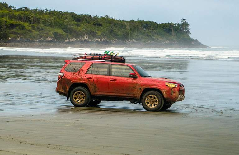 2016 Toyota 4Runner covered in mud driving in the sand along a water front
