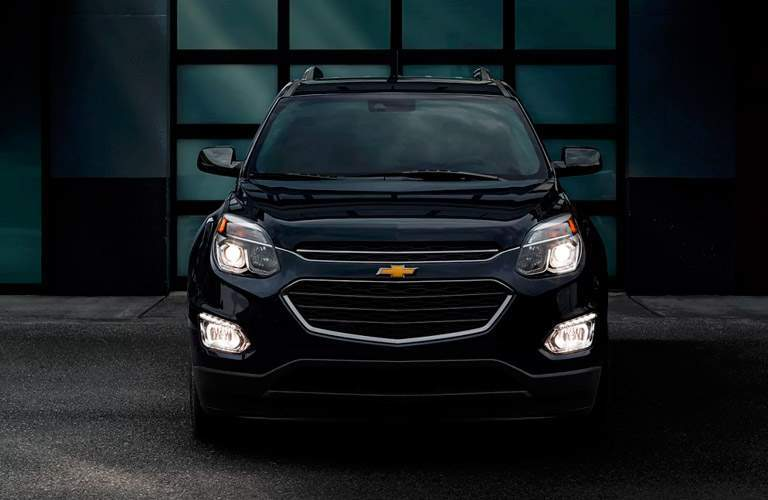 Front head on view of the 2017 Chevrolet Equinox in a dark room with the headlights on