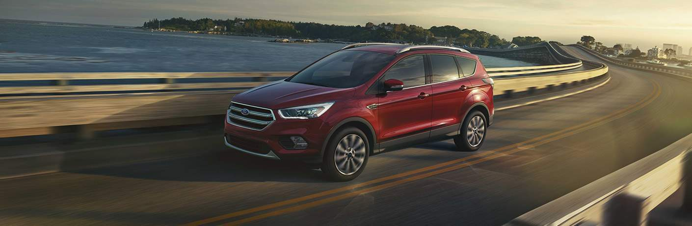 2017 Ford Escape driving on a winding highway next to a body of water with trees in the background