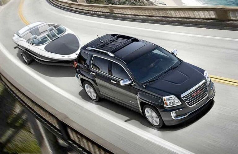 2017 GMC Terrain driving on a highway pulling a small boat on a trailer
