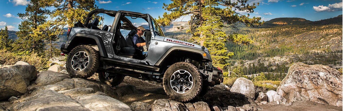 2017 Jeep Wrangler driving over rocky terrain in a mountainous area
