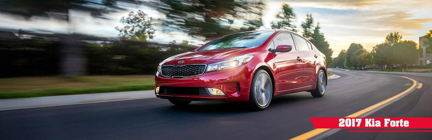 2017 Kia Forte driving on a highway passing trees