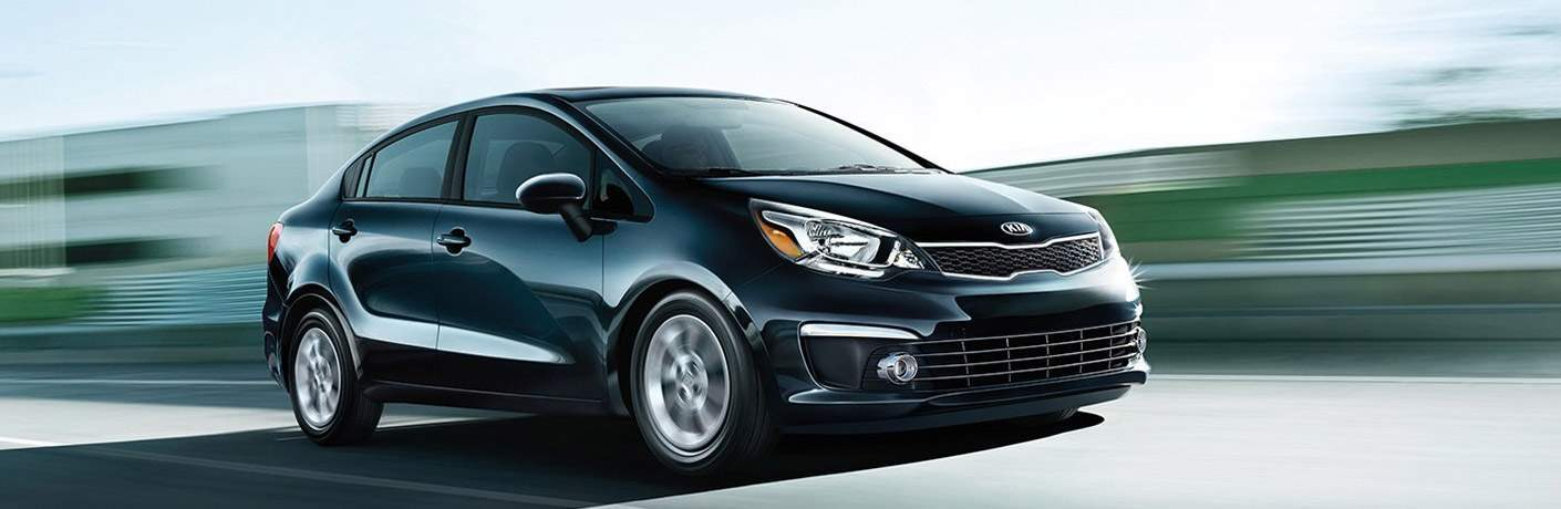 2017 Kia Rio driving on a road with a blurry greenish gray background