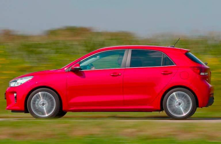 2017 Kia Rio hatchback driving in front of a blurry background of trees