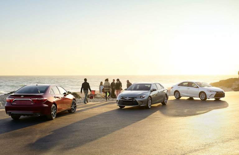 People gathering on a beach near three 2017 Toyota Camry vehicles