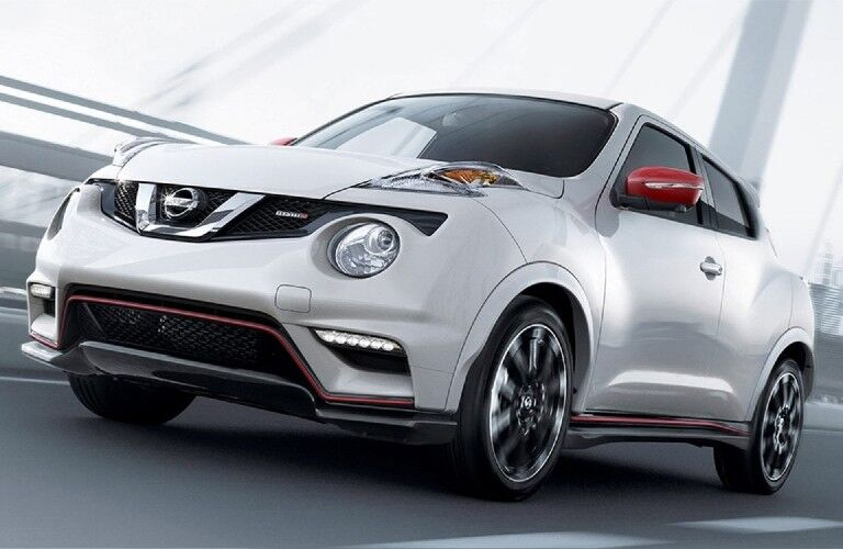 Front driver angle of a white 2017 Nissan JUKE driving on a road