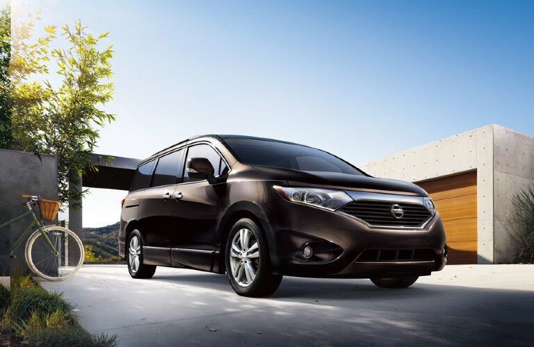 Front passenger angle of a black 2015 Nissan Quest parked by a home
