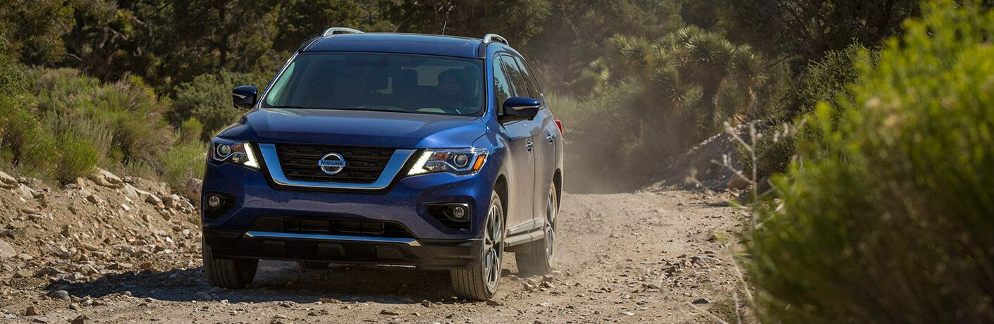 2017 Nissan Pathfinder driving on a rough, rocky trail in the wilderness