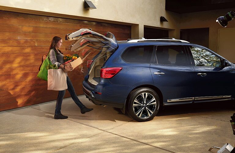Woman with her hands full opening the trunk of the 2017 Nissan Pathfinder with her foot