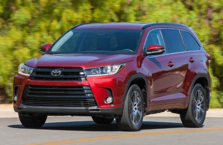 2017 Toyota Highlander driving on a road with trees in the background