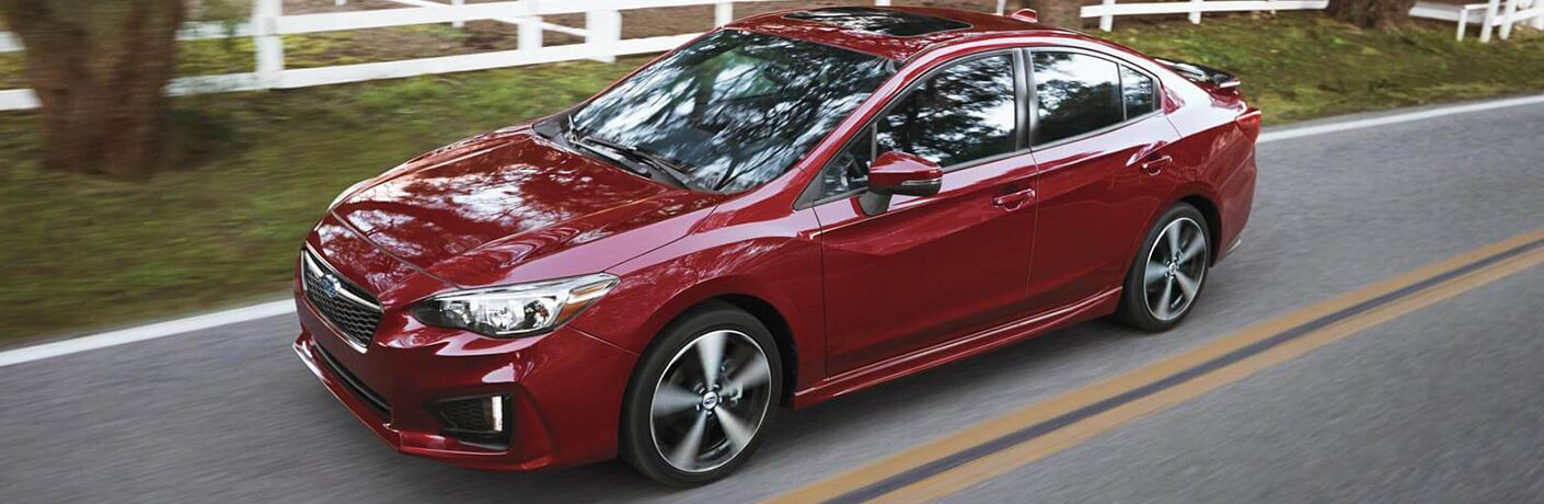 Front driver angle of a red 2019 Subaru Impreza driving down a road