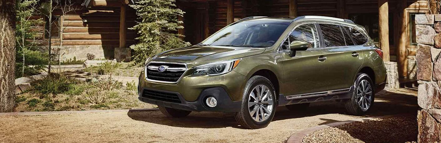 Front driver angle of a green 2019 Subaru Outback parked in front of a home