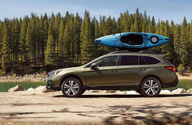 Driver angle of a green 2019 Subaru Outback parked outdoors with a kayak loaded on top