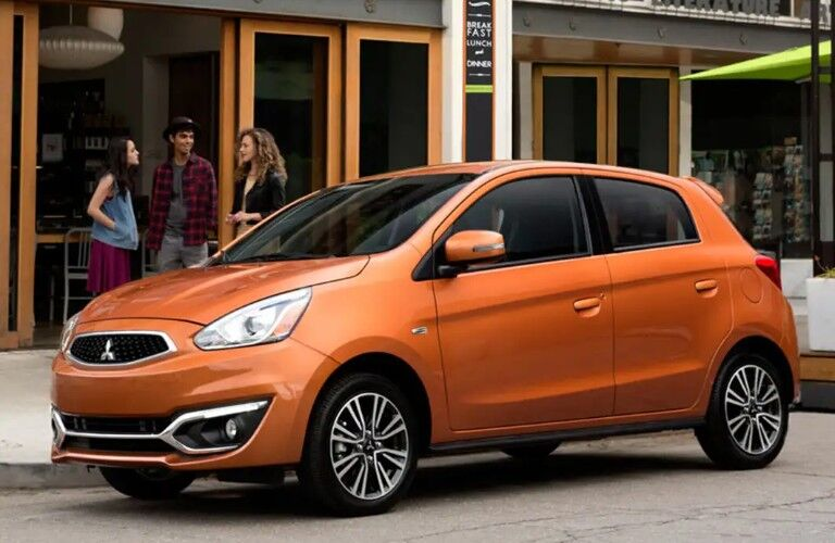 Front driver angle of an orange 2019 Mitsubishi Mirage parked on the side of a street with people standing behind it