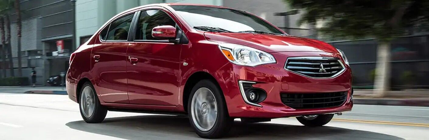 Front passenger angle of a red 2019 Mitsubishi Mirage G4 driving down a city street