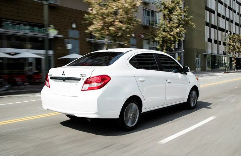 Rear passenger angle of a white 2019 Mitsubishi Mirage G4 driving down a road