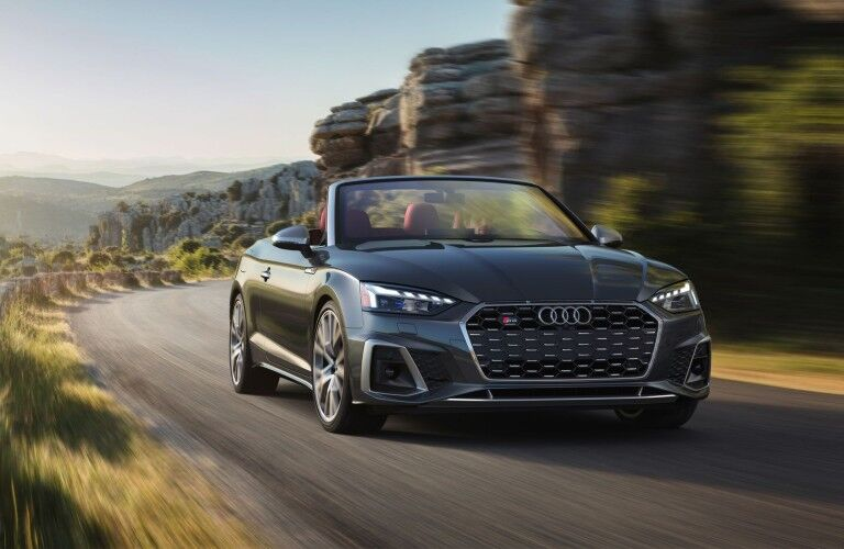 Front passenger angle of a grey 2020 Audi S5 Cabriolet driving down a road