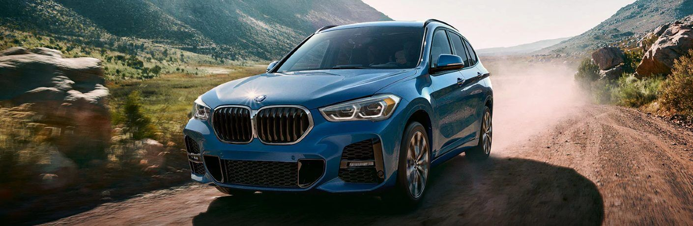 Front driver angle of a blue 2020 BMW X1 driving off-road