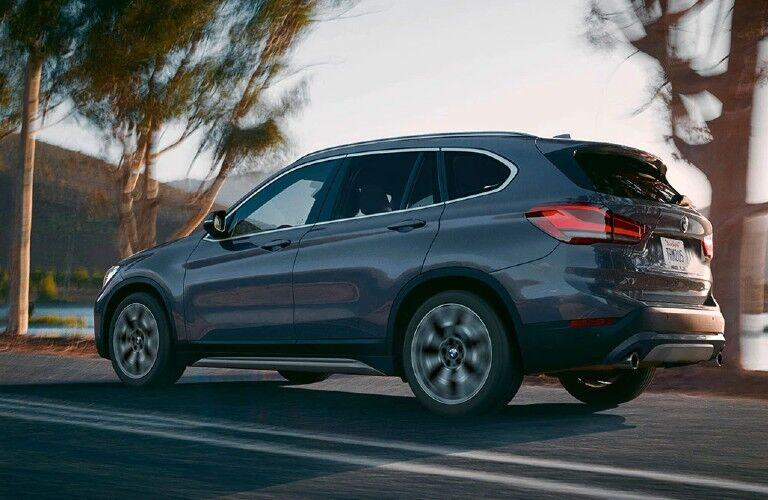 Rear driver angle of a grey 2020 BMW X1 driving on a road