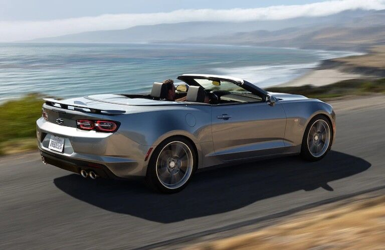 Rear passenger angle of a silver 2020 Chevrolet Camaro convertible driving by the ocean