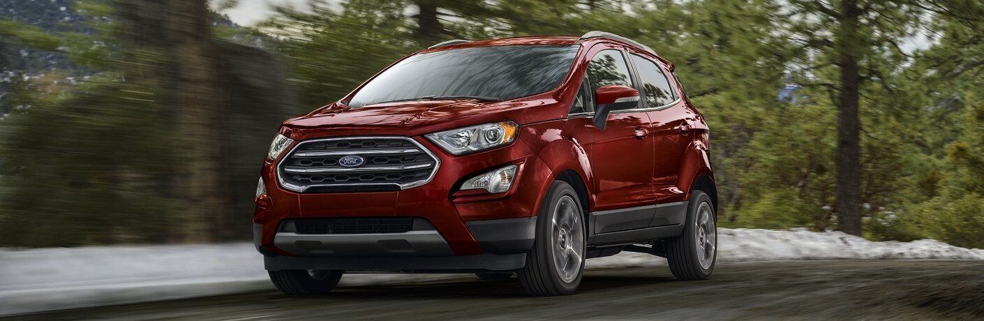 Front driver angle of a red 2020 Ford EcoSport driving on a road