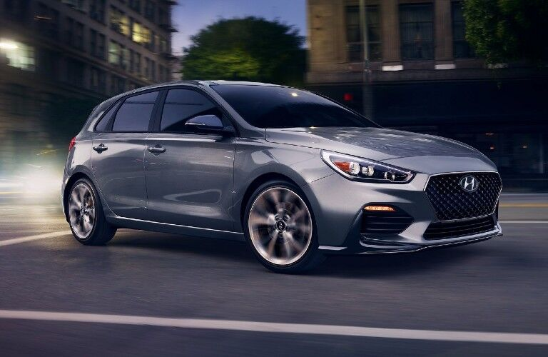 Front passenger angle of a grey 2020 Hyundai Elantra GT driving in a city