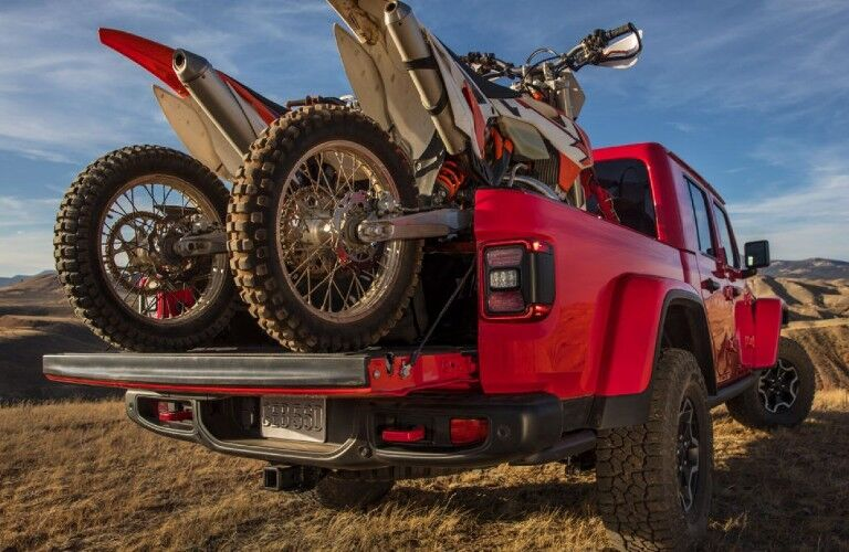 Rear passenger angle of a red 2020 Jeep Gladiator with dirt bikes loaded in the truck bed