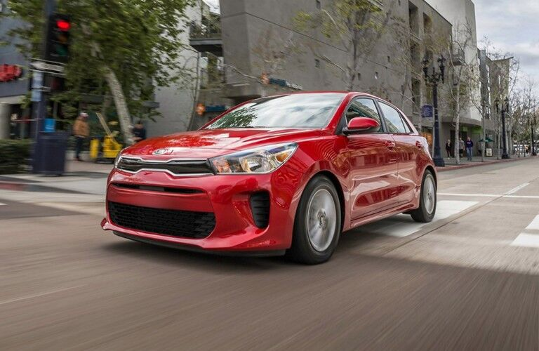 Front driver angle of a red 2020 Kia Rio 5-Door driving down a road