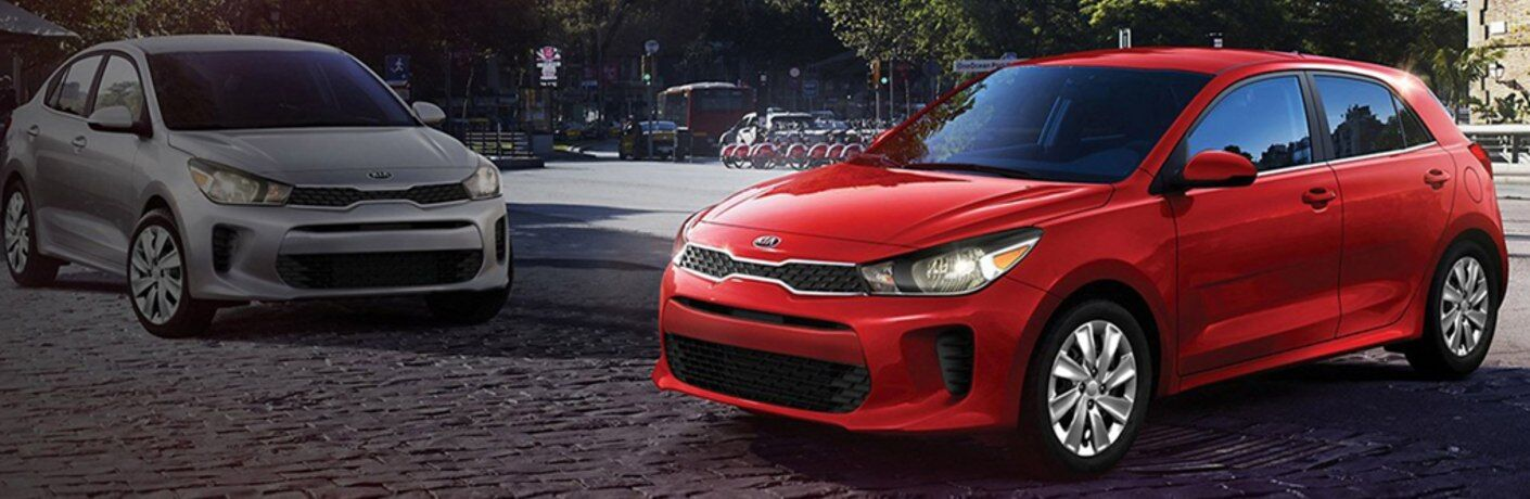 Red 2020 Kia Rio 5-Door parked near a silver 2020 Kia Rio 5-Door in a city