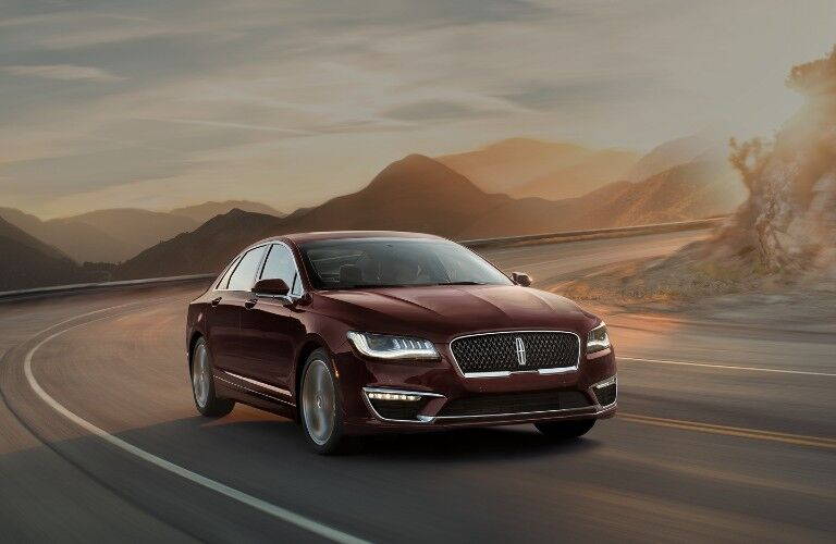 Front passenger angle of a maroon 2020 Lincoln MDZ driving down a road