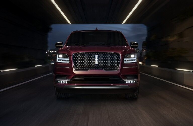 Front angle of a red 2020 Lincoln Navigator driving on a road