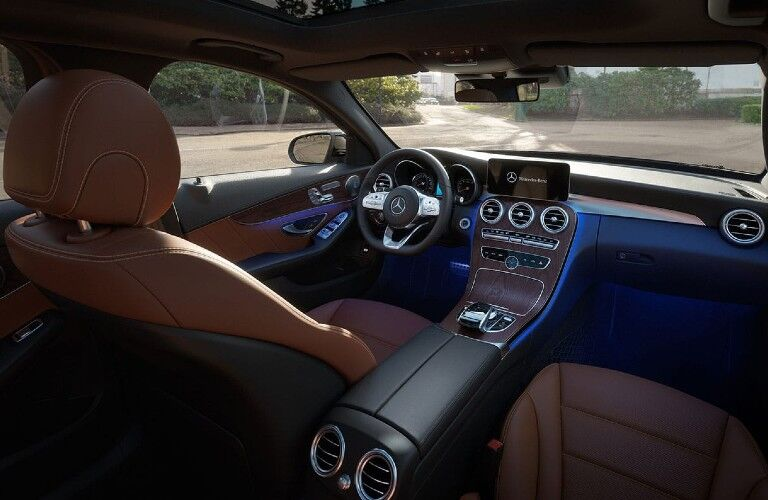 Front interior inside the 2020 Mercedes-Benz C-Class with blue ambient lighting
